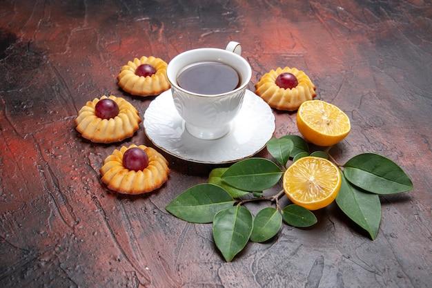 Vooraanzicht kopje thee met kleine koekjes op donkere achtergrond