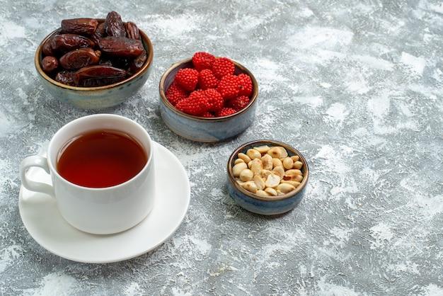 Vooraanzicht kopje thee met noten en confitures op witte ruimte