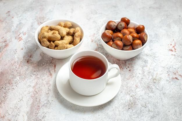 Vooraanzicht kopje thee met pinda's en hazelnoten op witte ruimte