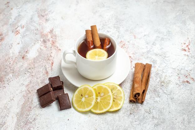 Vooraanzicht kopje thee met plakjes citroen en chocolade op witte ruimte