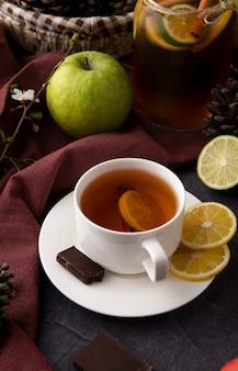 Vooraanzicht kopje thee met plakjes citroen en donkere chocolade met een groene appel op tafel