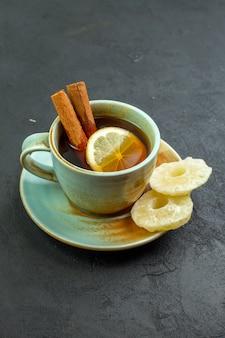 Vooraanzicht kopje thee met schijfjes citroen op donkere ondergrond