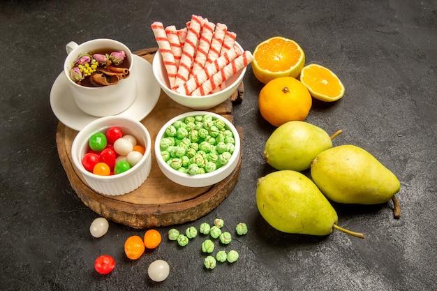 Vooraanzicht kopje thee met snoepjes, peren en mandarijnen op donkere ruimte