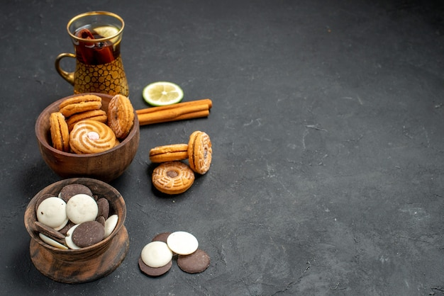 Vooraanzicht kopje thee met verschillende koekjes op een grijze achtergrond