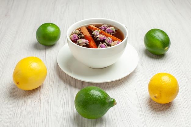 Vooraanzicht kopje thee met verse citroenen op wit bureau thee fruit citrus kleur Gratis Foto