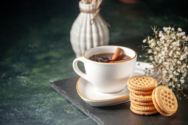 Vooraanzicht kopje thee met zoete koekjes op donkere ondergrond brood drinken ceremonie glas zoet ontbijt cake kleur suiker ochtend