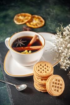 Vooraanzicht kopje thee met zoete koekjes op donkere ondergrond brood drinken ceremonie glas zoet ontbijt cake kleurenfoto ochtend