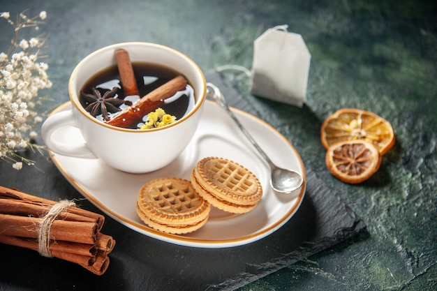 Vooraanzicht kopje thee met zoete koekjes op donkere ondergrond brood drinken ceremonie glas zoet ontbijt ochtend suiker cake kleurenfoto's