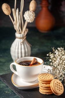 Vooraanzicht kopje thee met zoete koekjes op donkere ondergrond brood drinken ceremonie glas zoete cake kleurenfoto suiker ochtend