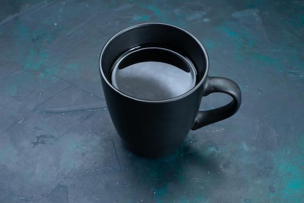 Vooraanzicht kopje thee op de donkerblauwe kleur van de theedrank op het bureau
