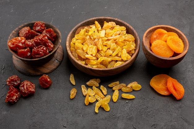 Vooraanzicht krenten en rozijnen met gedroogde abrikozen in kleine potten op grijze ruimte