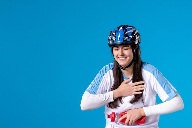 Vooraanzicht lachen jong wijfje in sportkleren en helm op blauw