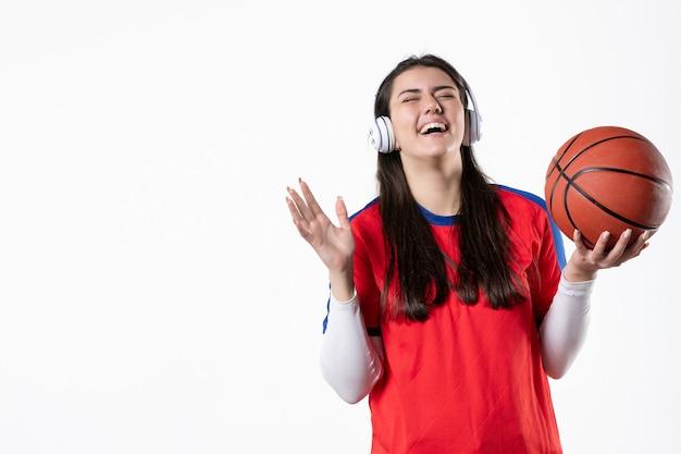 Vooraanzicht lachen jong wijfje in sportkleren met basketbal