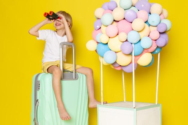 Vooraanzicht lachend kind blonde haren zittend op de blauwe tas, samen met kleurrijke lucht ballonnen op gele vloer