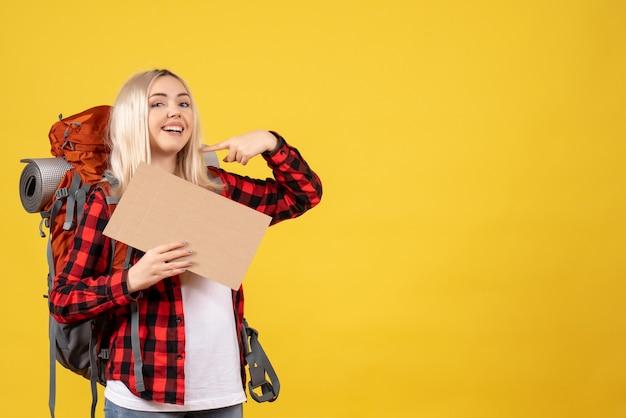 Vooraanzicht lachende blonde reizigersvrouw met haar rugzak met karton staande op gele muur