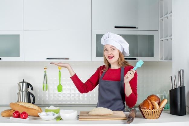 Vooraanzicht lachende blonde vrouw in kok hoed en schort met borstel in de keuken