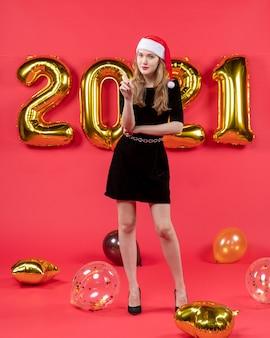 Vooraanzicht lachende jonge dame in zwarte jurk ballonnen op rood