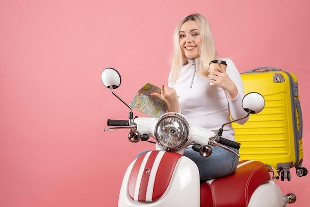 Vooraanzicht lachende jonge dame op bromfiets met gele koffer met kaart en koffiekopje