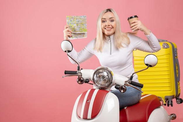 Vooraanzicht lachende jonge dame op bromfiets met koffiekopje en kaart
