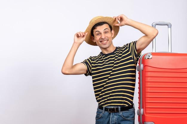 Vooraanzicht lachende jonge man die in de buurt van rode koffer zijn hoed vasthoudt