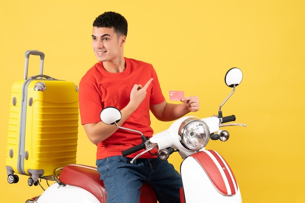Vooraanzicht lachende jonge man in rood t-shirt op bromfiets met creditcard