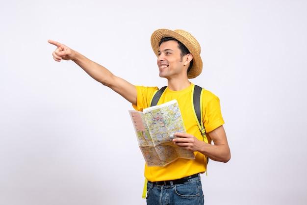 Vooraanzicht lachende jonge man met geel t-shirt en strooien hoed wijzend op iets