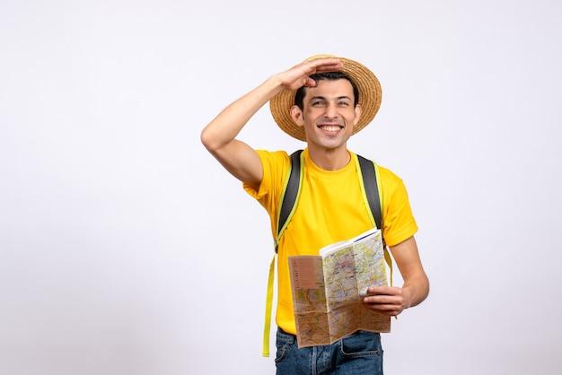 Vooraanzicht lachende jonge man met gele t-shirt en strooien hoed camera kijken