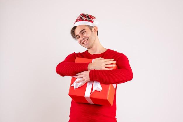 Vooraanzicht lachende jonge man met kerstmuts zijn gift strak op wit te houden