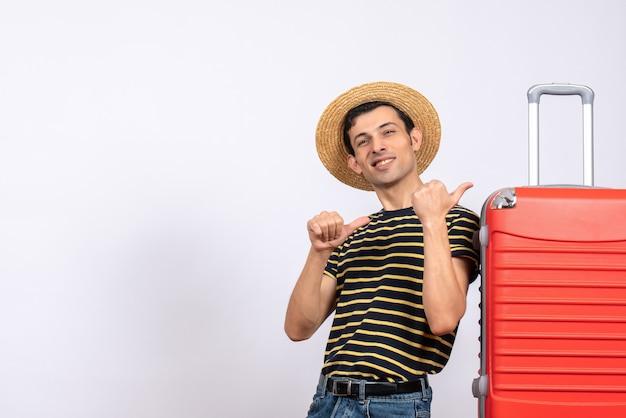 Vooraanzicht lachende jonge man met strooien hoed staande in de buurt van koffer