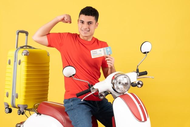 Vooraanzicht lachende jonge man op bromfiets bedrijf kaartje weergegeven: armspier