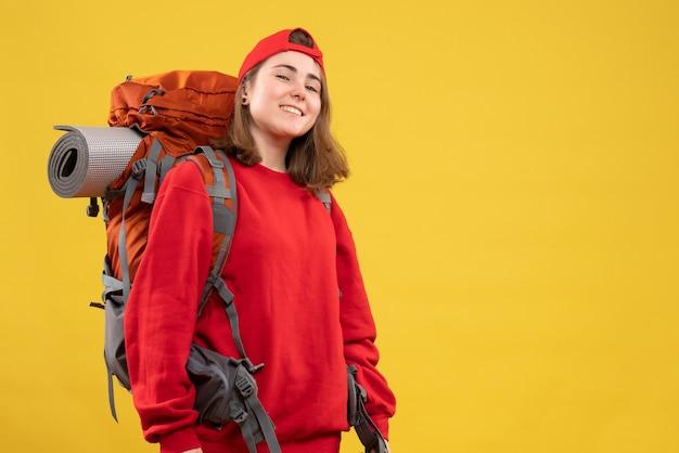 Vooraanzicht lachende jonge toerist met rugzak en rode dop