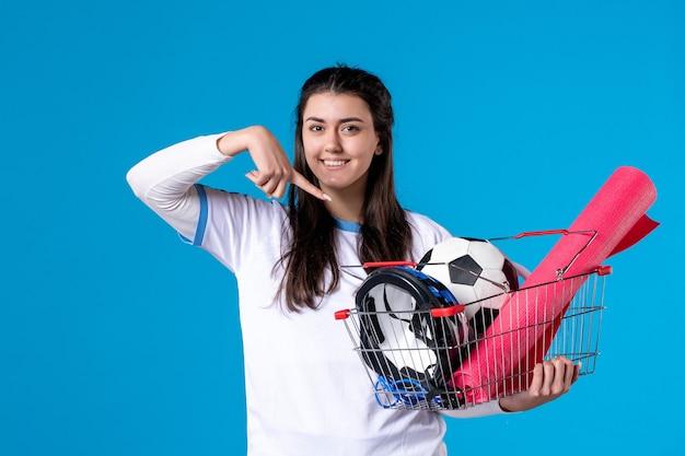 Vooraanzicht lachende jonge vrouw met mand vol sport dingen