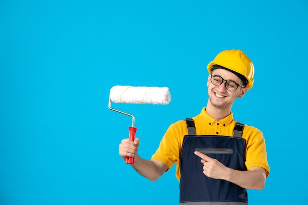 Vooraanzicht lachende mannelijke bouwer in uniform en helm met verfroller op een blauw