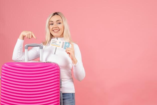 Vooraanzicht lachende mooie vrouw met roze koffer met vliegticket