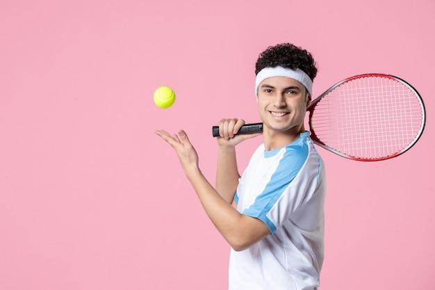 Vooraanzicht lachende tennisser in de racket van sportkleding