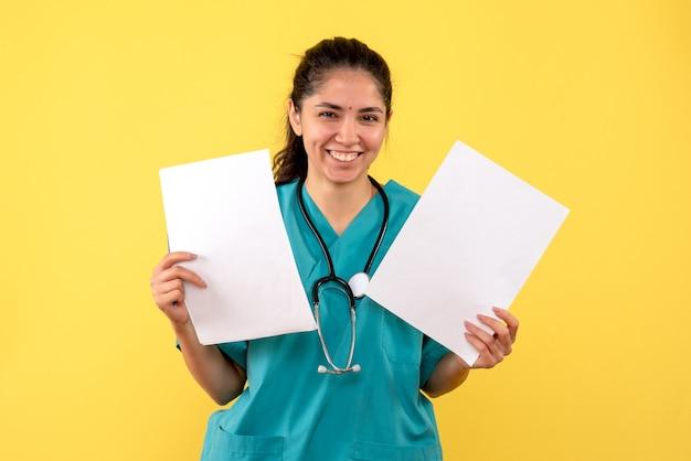 Vooraanzicht lachende vrouw arts in uniform met papieren in beide handen op gele achtergrond
