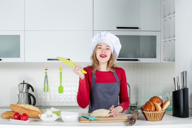 Vooraanzicht lachende vrouw in kok hoed en schort met mes in de keuken