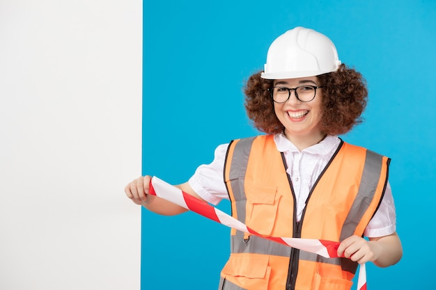 Vooraanzicht lachende vrouwelijke bouwer in uniform op blauw