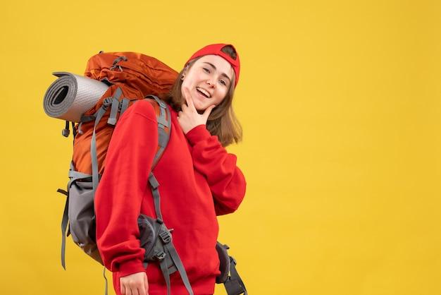 Vooraanzicht lachende vrouwelijke reiziger met rugzak hand op haar kin te zetten