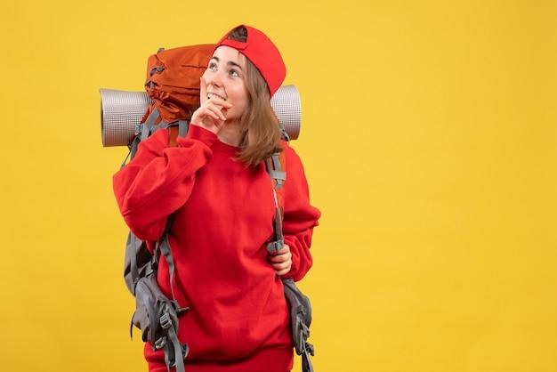 Vooraanzicht lachende vrouwelijke reiziger met rugzak iets staren