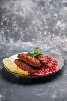 Vooraanzicht lange vleeskoteletten met citroen en granaatappels