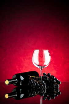 Vooraanzicht leeg wijnglas met donkere druiven op de roze achtergrond