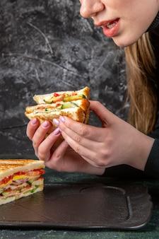 Vooraanzicht lekker broodje ham eten krijgen door vrouwtje op donkere ondergrond