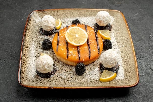 Vooraanzicht lekker cakedessert met schijfjes citroen en kokossnoepjes op donkere achtergrond taartdessert thee zoete cake snoep