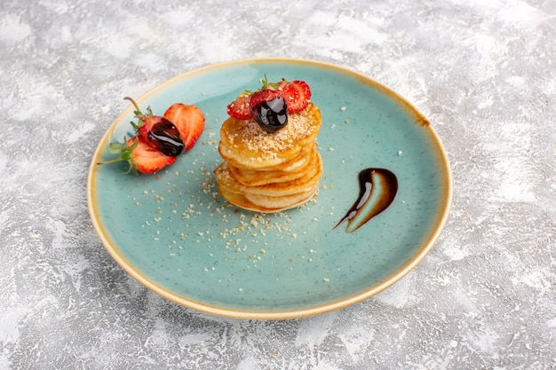 Vooraanzicht lekker gebak zoet met aardbeien in plaat op de witte tafel, zoete suiker bakken gebak
