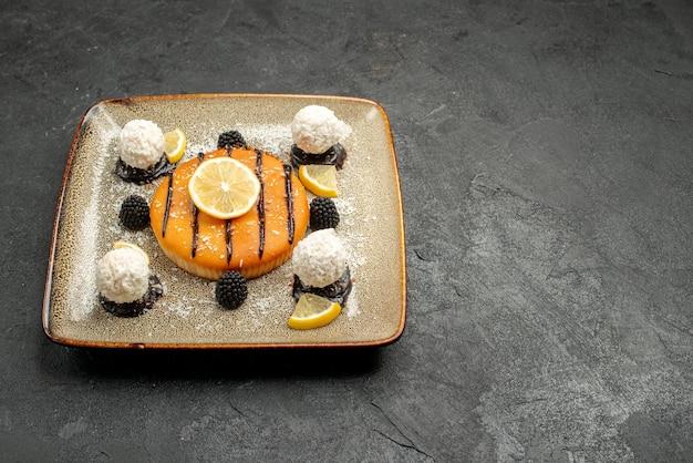 Vooraanzicht lekker taartdessert met schijfjes citroen en kokossnoepjes op donkere achtergrond taart dessert zoete taart snoep thee