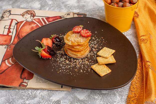 Vooraanzicht lekkere chips ontworpen met aardbeien in plaat op witte tafel, chips snack fruitbes