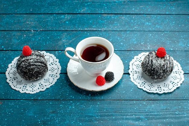Vooraanzicht lekkere chocoladeballen met kopje thee op het blauwe rustieke van het de cakekoekje van de bureauthee het koekjeskoekje