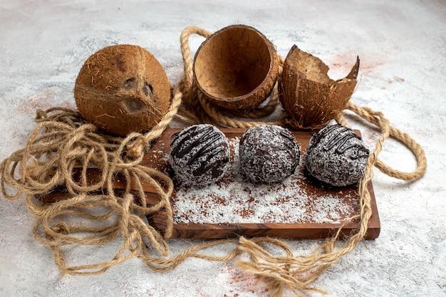 Vooraanzicht lekkere chocoladetaartjes met kokos op het lichtwitte oppervlak bak biscuit suikertaart zoete koekjeschocolade