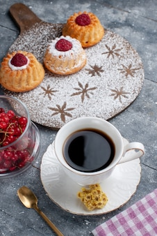 Vooraanzicht lekkere d cakes met kopje koffie en verse rode veenbessen op het grijze bureau zoete fruit